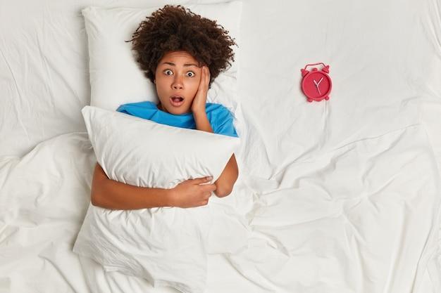 Jeune femme brune couchée dans son lit