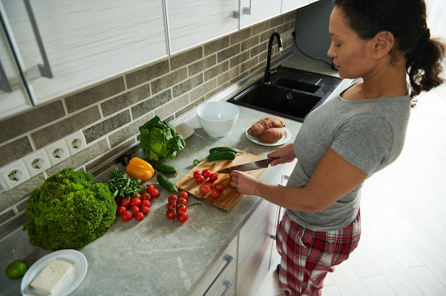 Jeune femme brune coupant des tomates pour préparer une salade saine végétalienne.