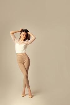 Jeune femme brune en crop top et pantalon skinny posant et regardant l'avant sur une surface beige