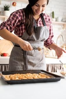 Jeune femme brune la cuisson des cookies dans la cuisine, verser la poudre de cacao