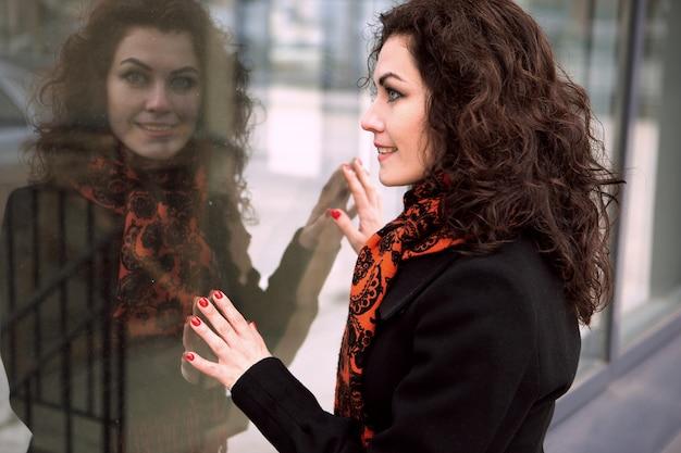 Une jeune femme brune dans une écharpe lumineuse et un manteau sombre se penche sur le reflet d'un énorme verre
