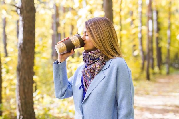 Jeune femme brune dans un manteau bleu debout dans le parc avec une tasse de café