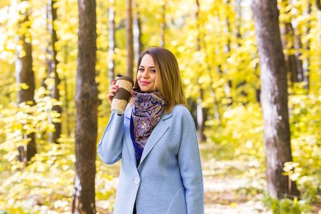 Jeune femme brune dans un manteau bleu debout dans le parc avec une tasse