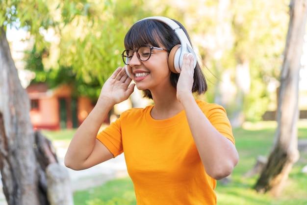 Jeune femme brune dans le parc écoutant de la musique et chantant
