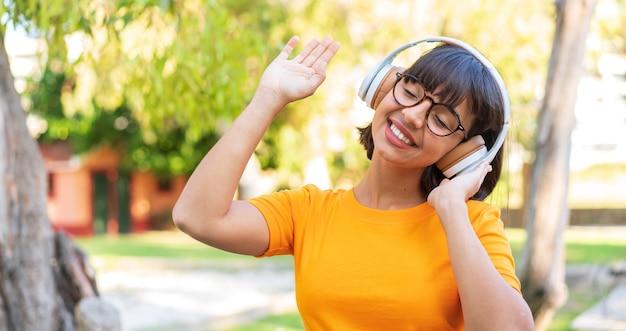 Jeune femme brune dans le parc, écouter de la musique et danser