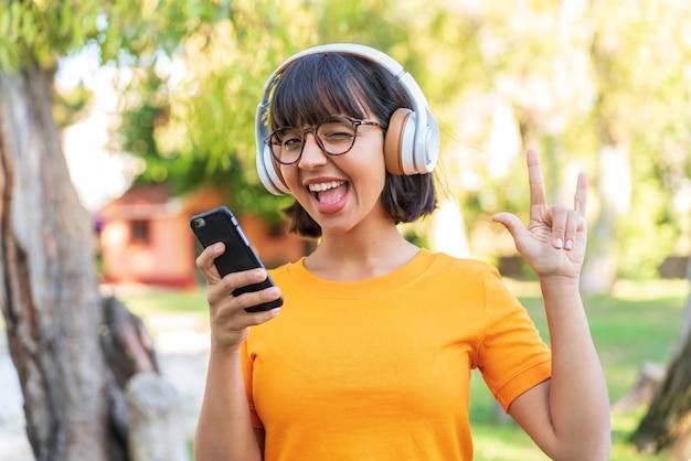 Jeune femme brune dans le parc, écouter de la musique avec un mobile faisant un geste rock