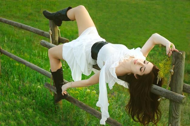 Jeune femme brune dans une robe blanche se trouve sur une clôture en bois à la frontière de la ferme.