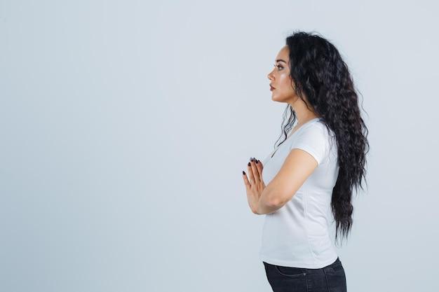Jeune femme brune dans un t-shirt blanc priant