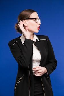 Jeune femme brune dans une veste avec du rouge à lèvres sur les lèvres