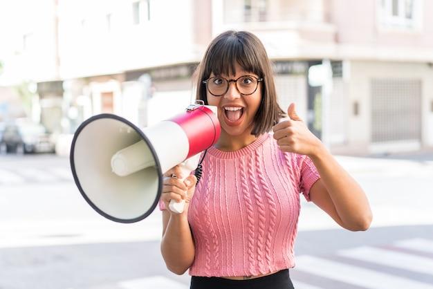 Jeune femme brune dans la ville criant à travers un mégaphone pour annoncer quelque chose et avec le pouce vers le haut