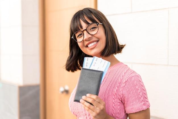 Jeune femme brune dans la ville heureuse en vacances avec passeport et billets d'avion