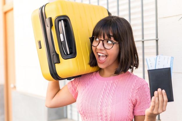 Jeune femme brune dans la ville en vacances avec valise et passeport