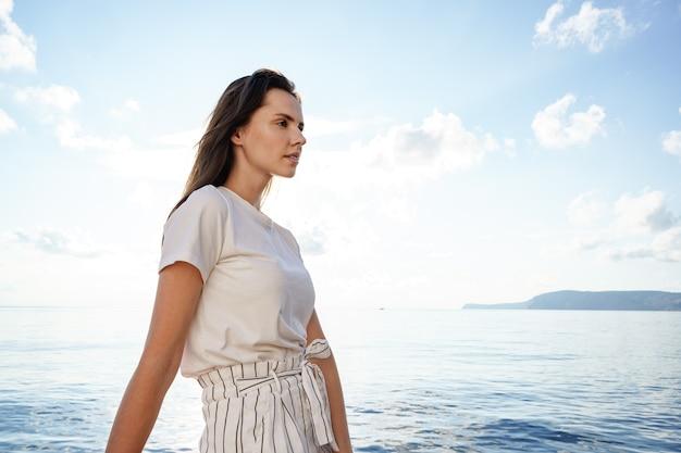 Jeune femme brune debout sur le nez du yacht lors d'une journée d'été ensoleillée
