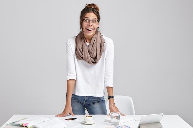 Jeune Femme Brune Debout Près Du Bureau Photo gratuit