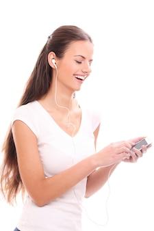 Jeune femme brune avec écouteurs et smartphone