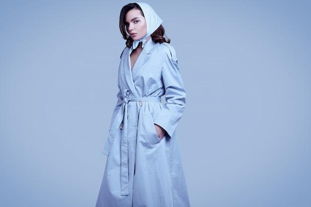Jeune femme brune élégante en manteau et châle posant