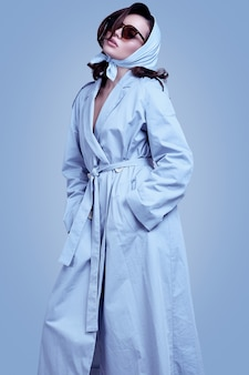 Jeune femme brune élégante en manteau et châle qui pose en studio