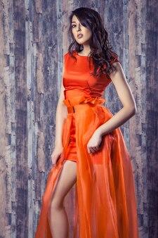 Jeune femme brune en élégante robe de soie orange posant sur fond de bois