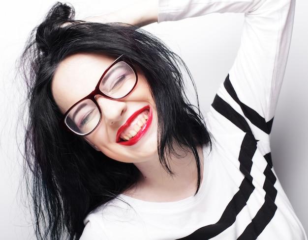 Jeune femme brune émotionnelle porte des lunettes