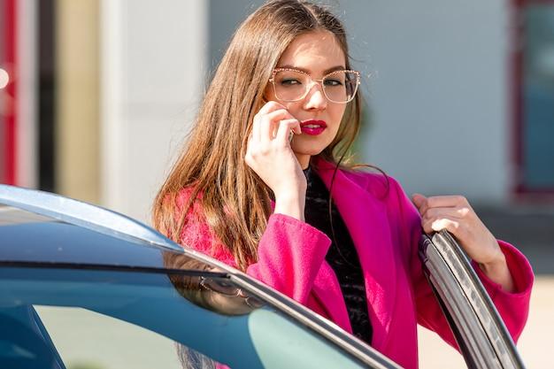 Jeune femme brune émotionnelle sort de la voiture et parle au téléphone