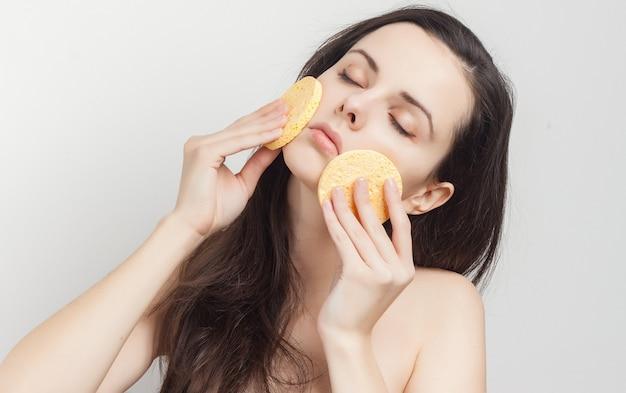Jeune femme brune avec des éponges pour nettoyer la peau de ses mains, fond clair