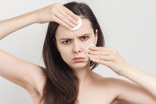 Jeune femme brune avec des éponges pour nettoyer la peau de ses mains