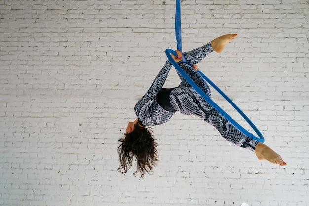 Une jeune femme brune est engagée dans des acrobaties aériennes dans un survêtement sur une brique blanche.
