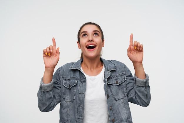Jeune femme brune étonnée heureuse porte en t-shirt blanc et vestes en jean, lève les yeux et sourit largement, pointe du doigt sur l'espace de copie, se dresse sur fond blanc.