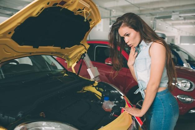 La jeune femme brune examine la voiture chez le concessionnaire et fait son choix.