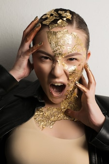 Jeune femme brune expressive avec le maquillage d'imagination