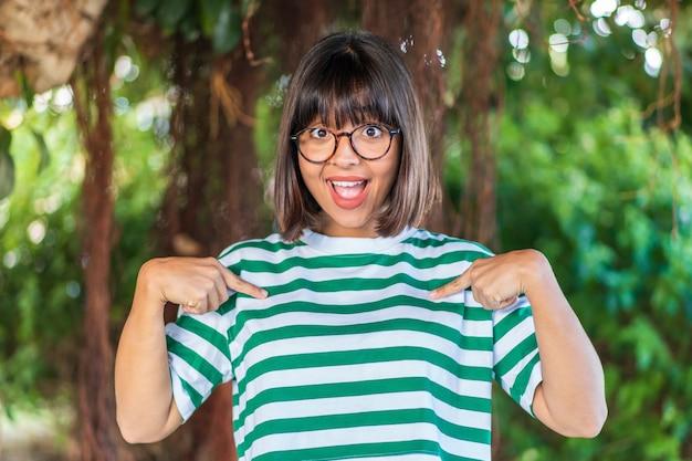 Jeune femme brune à l'extérieur dans un parc avec une expression faciale surprise