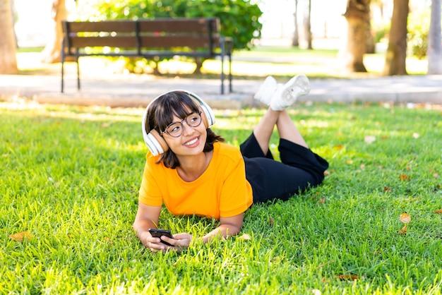 Jeune femme brune à l'extérieur en écoutant de la musique avec le mobile et heureuse