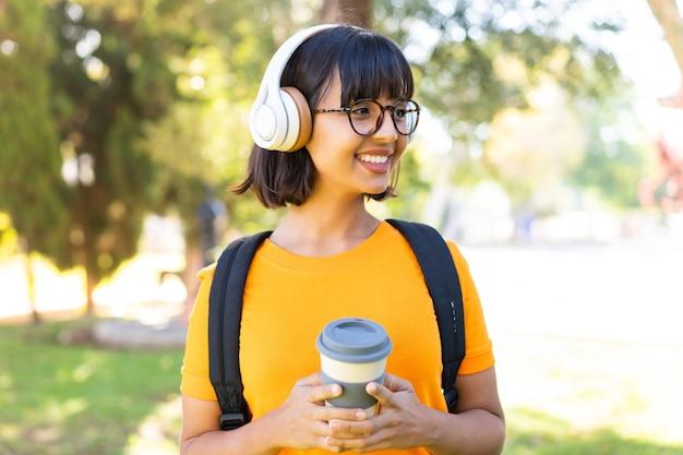 Jeune femme brune à l'extérieur, écoutant de la musique et tenant un café à emporter