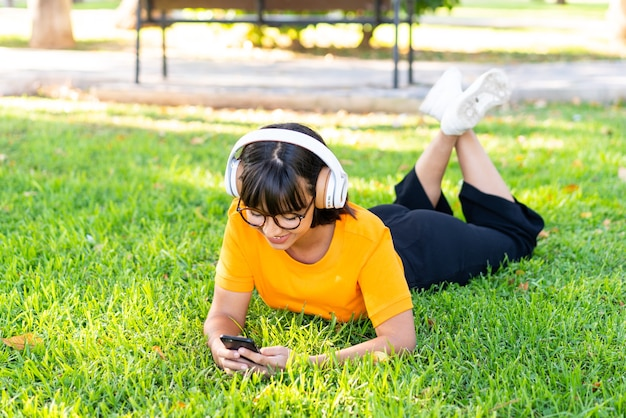 Jeune femme brune à l'extérieur, écouter de la musique avec le mobile