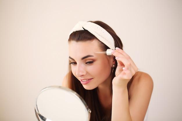 Jeune femme brune faisant ses soins de la peau dans le miroir