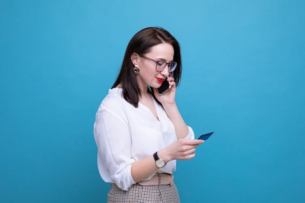 Une jeune femme brune fait une commande en ligne à l'aide de son téléphone et de sa carte bancaire