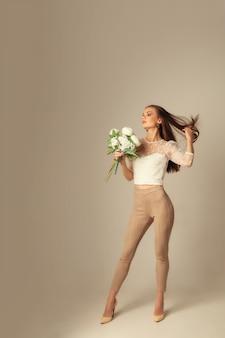 Jeune femme brune avec des fleurs posant et regardant l'avant sur une surface beige