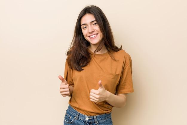 Jeune femme brune sur un fond beige, levant les deux pouces, souriant et confiant.