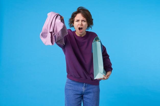 Jeune femme brune frisée aux yeux bruns mécontents, levant la main avec des vêtements