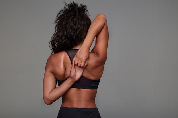 Jeune femme brune frisée à la peau foncée sportive avec une coiffure décontractée en pliant les bras derrière le dos tout en faisant de l'entraînement du matin, isolé