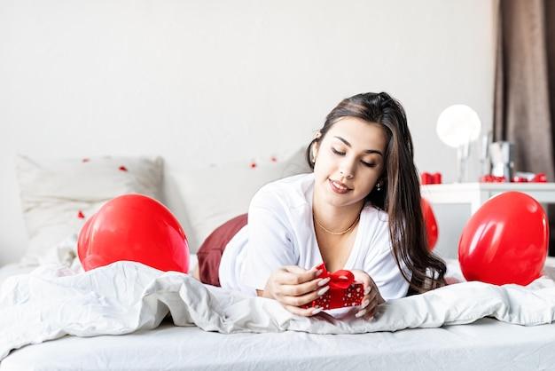 Jeune femme brune heureuse pose dans le lit avec des ballons en forme de coeur rouge déballant le présent