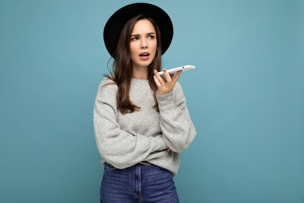 Jeune femme brune insatisfaite demandant un chapeau noir et un pull gris tenant un smartphone regardant sur le côté isolé sur fond.