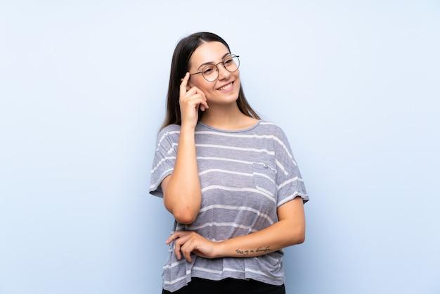 Jeune femme brune isolée bleue avec des lunettes
