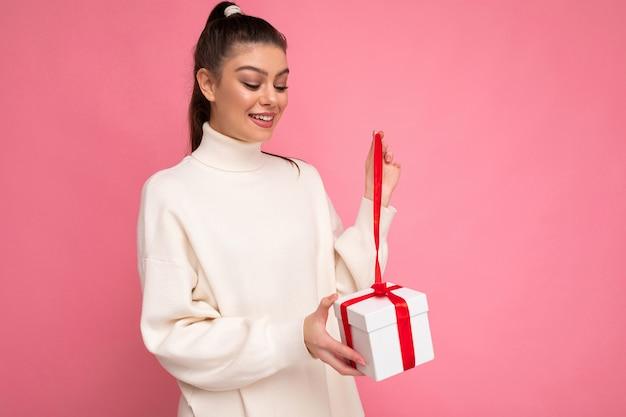 Jeune femme brune isolée sur mur de fond rose portant un chandail blanc tenant une boîte-cadeau et unboxing présente à la boîte.