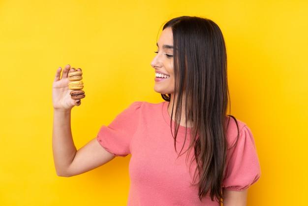 Jeune femme brune sur jaune tenant des macarons colorés et heureux