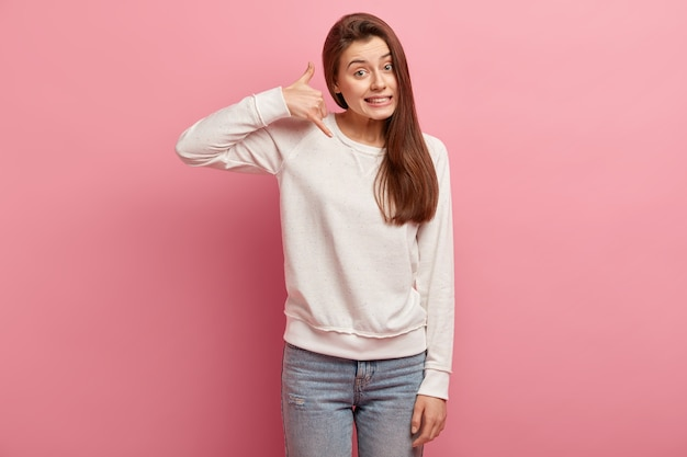 Jeune femme brune en jeans et pull
