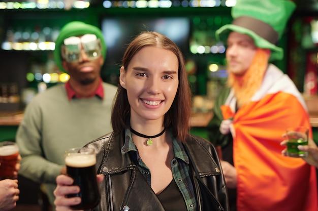 Jeune femme brune joyeuse vous regarde tout en grillant avec un verre de bière contre des gars en chapeaux verts assis près du comptoir du bar