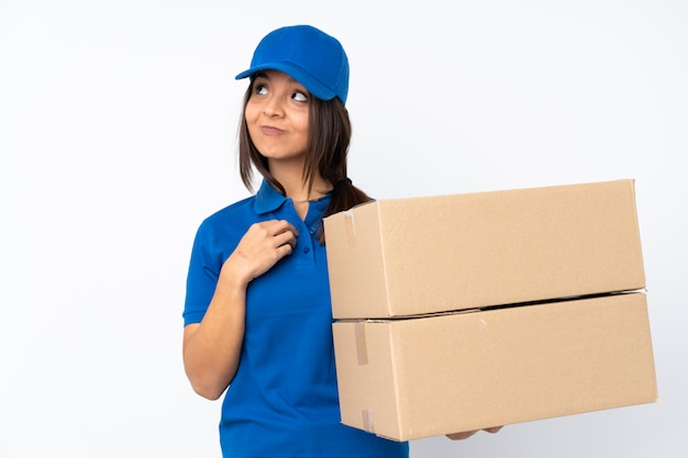 Jeune femme brune de livraison sur mur blanc isolé complotant quelque chose