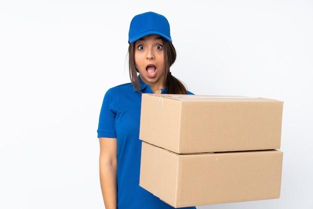 Jeune femme brune de livraison sur un mur blanc isolé avec une expression faciale surprise