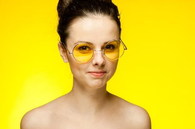 Jeune femme brune à lunettes jaunes, portrait sur un espace jaune